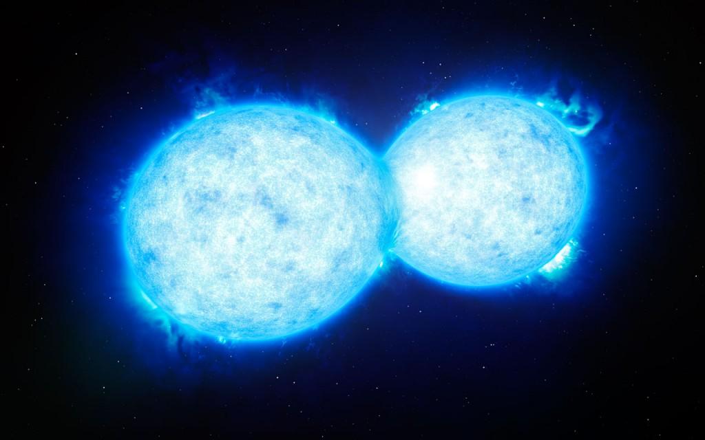 Esta impressão artística mostra o VFTS 352 — o sistema binário mais quente e mais massivo descoberto até à data, onde as duas componentes estão em contacto, partilhando material. As duas estrelas deste sistema extremo, que se situa a cerca de 160 000 anos-luz de distância na Grande Nuvem de Magalhães, podem estar a dirigir-se para um final dramático, no qual fusionam para formar uma única estrela gigante ou então dão origem um buraco negro binário. Créditos: ESO/L. Calçada
