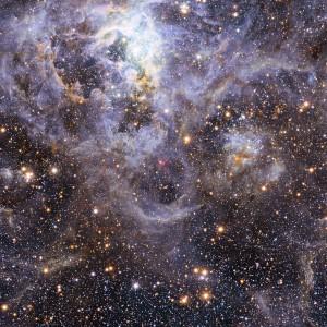 Esta imagem mostra a localização do VFTS 352 — o sistema binário mais quente e mais massivo descoberto até à data, onde as duas componentes estão em contacto, partilhando material. As duas estrelas deste sistema extremo, que se situa a cerca de 160 000 anos-luz de distância na Grande Nuvem de Magalhães, podem estar a dirigir-se para um final dramático, no qual fusionam para formar uma única estrela gigante ou então dão origem um buraco negro binário. Esta imagem da região de formação estelar da Tarântula inclui imagens no visível obtidas pelo instrumento Wide Field Imager montado no telescópio MPG/ESO de 2,2 metros em La Silla e imagens no infravermelho do telescópio infravermelho VISTA de 4,1 metros situado no Paranal. Créditos: ESO/M.-R. Cioni/VISTA Magellanic Cloud survey. Acknowledgment: Cambridge Astronomical Survey Unit