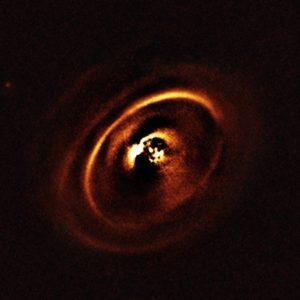 Com o auxílio do instrumento SPHERE do ESO, montado no Very Large Telescope, uma equipa de astrónomos observou o disco planetário que rodeia a estrela RXJ1615, situada na constelação do Escorpião, a 600 anos-luz de distância da Terra. As observações mostraram um sistema complexo de anéis concêntricos em torno da estrela jovem, criando uma forma que parece uma versão titânica dos anéis que rodeiam Saturno. No passado, apenas se obtiveram algumas imagens de uma tão intricada escultura de anéis num disco protoplanetário.  Créditos:  ESO, J. de Boer et al.